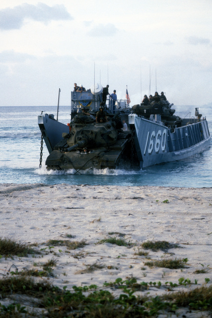 Members of the 26th Marine Amphibious Unit drive two M60 main battle tanks off utility landing craft 1660 (LCU 1660) at Vieques Island during Operation OCEAN VENTURE '84