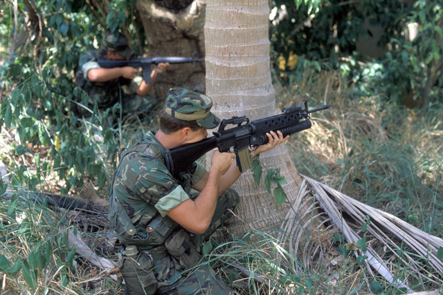 """Security policemen air their M16 rifles toward an """"enemy objective"""" during Operation OCEAN VENTURE '84. The M16 in the foreground is equipped with an M203 grenade launcher"""