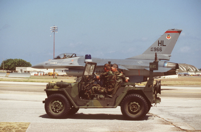 Security policemen sit in an M151 light utility vehicle on the runway apron during Operation OCEAN VENTURE '84. An F-16 Fighting Falcon aircraft, assigned to the 34th Tactical Fighter Squadron, 388th Tactical Fighter Wing is visible in the background