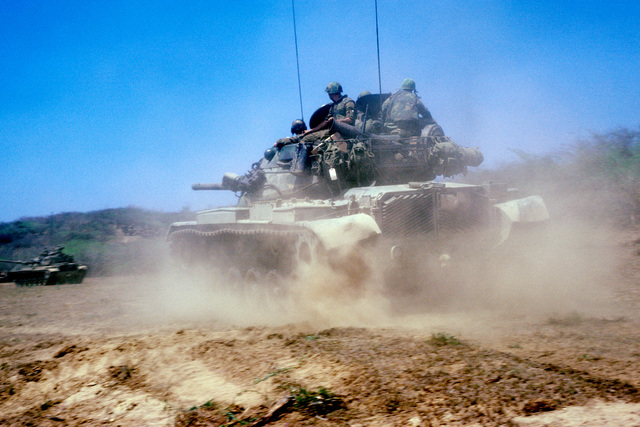 Two US Marine Corps M60A1 main battle tanks move forward during Exercise OCEAN VENTURE '84