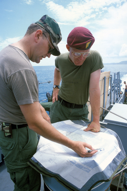 Warrant Officer Charles Brooks, left, talks with Second Lieutenant William Hardwick, tank platoon leader, 3rd Platoon, Company B, 82nd Airborne Division, about the route they will be taking to Viegues Island while underway aboard a utility landing craft during Operation OCEAN VENTURE '84
