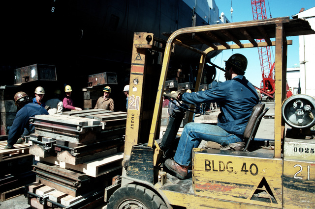Shipyard workers remove support blocks from under the Safeguard class salvage ship GRASP (ARS 51) to be taken away by forklift, in preparation for its launching at Peterson Builders Inc