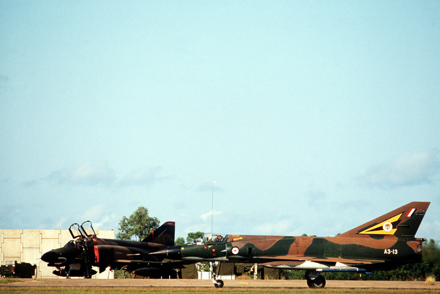 A left side view of an RAAF Mirage III-D (French designed) aircraft, right, taxiing by a US F-4 Phantom II aircraft parked on the flight line during the joint Australia/New Zealand/US Exercise PITCH BLACK '84