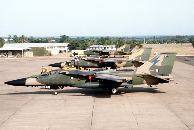 A left side view of three RAAF F-111 Fighter aircraft parked on the flight line during the joint Australia/New Zealand/US Exercise PITCH BLACK '84