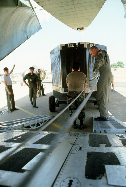 A member of the 15th Military Airlift Squadron pulls out a pulley and cable during the loading of equipment aboard a C-141B Starlifter aircraft during Pitch Black '84. Pitch Black is a joint U.S., Australian and New Zealand exercise