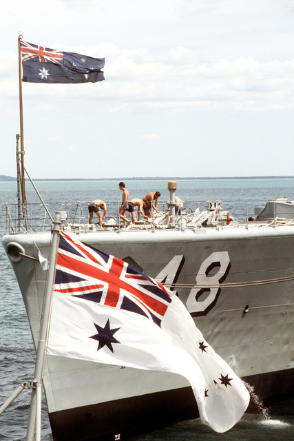 A port bow view of the Australian frigate HMAS STUART (D 48) framed by the Australian flag. The ship is operating with the US and New Zealand Navies during Exercise PITCH BLACK '84