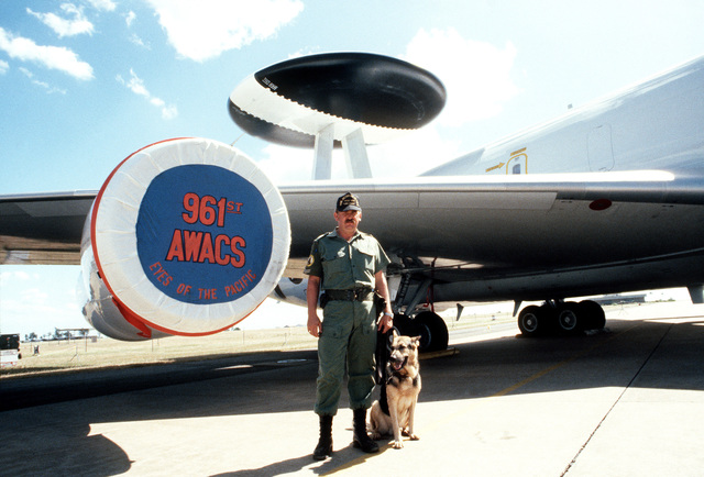 A RAAF security policeman and his German shepherd stand guard in front of an E-3A Sentry Airborne Early Warning and Control System (AWACS) aircraft, assigned to the 961st AWACS Squadron, during the joint Australia/New Zealand/US Exercise PITCH BLACK '84