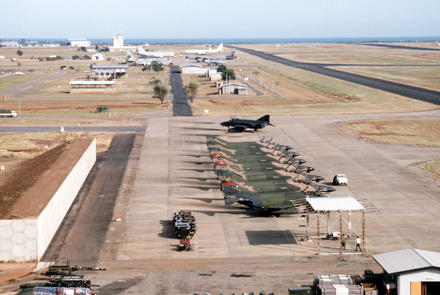 Aerial view of the flight line during PITCH BLACK 84, a joint US, Australian and New Zealand exercise. In the foreground are F-4 aircraft, followed by a B-52 Stratofortress, an Australian transport, and E-3A Sentry AWACS (Airborne Warning and Control System) and KC-135 Stratotanker aircraft, left