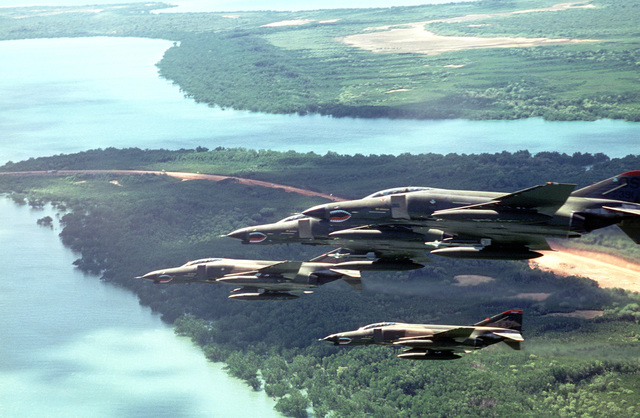 An air-to-air left side view of five F-4 Phantom II aircraft from the 51st Tactical Fighter Wing. The aircraft are being used during PITCH BLACK 84, a joint US, Australian and New Zealand exercise