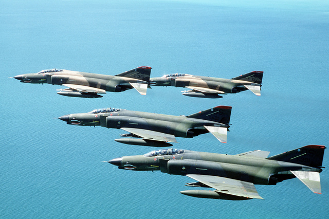An air-to-air left side view of four F-4 Phantom II aircraft from the 51st Tactical Fighter Wing. The top two aircraft are armed with AIM-9 Sidewinder air-to-air missiles. The aircraft are being used during PITCH BLACK 84, a joint US, Australian and New Zealand exercise
