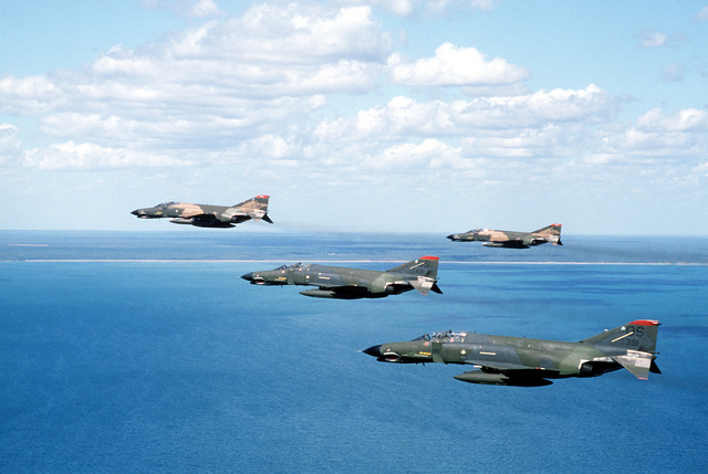 An air-to-air left side view of four F-4 Phantom II aircraft from the 51st Tactical Fighter Wing. The aircraft are being used during PITCH BLACK 84, a joint US, Australian and New Zealand exercise