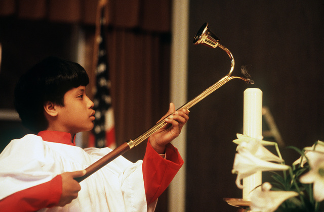 An altar boy lights a candle during Easter Sunday services at the North Chapel