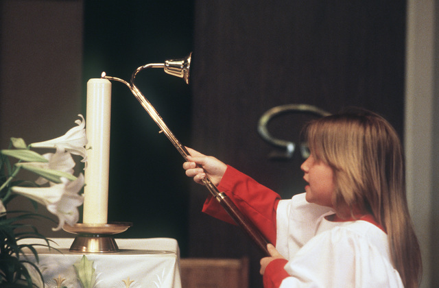 An altar girl lights a candle during Easter Sunday services at the North Chapel