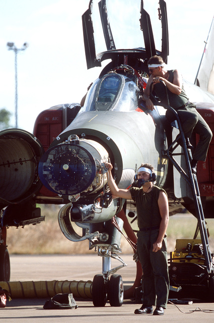 Ground crew members from the 51st Tactical Fighter Wing perform maintenance on an F-4 Phantom II aircraft during Exercise PITCH BLACK 84, a joint US, Australian and New Zealand exercise