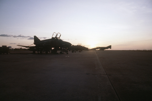 Silhouetted left side view of an F-4 Phantom II aircraft taxiing onto the runway apron after a mission. The aircraft is being used during PITCH BLACK 84, a joint US, Australian and New Zealand exercise. Other F-4 aircraft are parked on the left