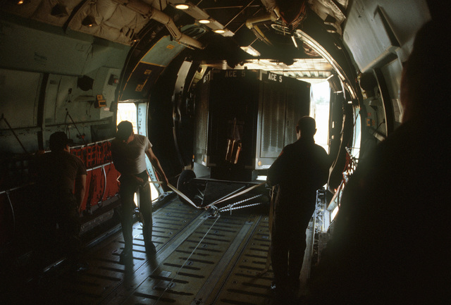 Two members of the 15th Military Airlift Squadron load a piece of equipment aboard a C-141B Starlifter aircraft during Pitch Black '84. Pitch Black is a joint U.S., Australian and New Zealand exercise