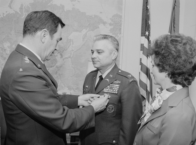 Lieutenant General (LGEN) Philip C. Gast, director of the Defense Security Assistance Agency (DSAA), pins the Defense Superior Service Medal on Colonel (COL) Fred Raines, currently acting deputy director for operations, DSAA.  The medal was awarded for duties performed while serving as defense and Army attache in Tel Aviv, Israel.  The Colonel's wife, Polly, is on the right