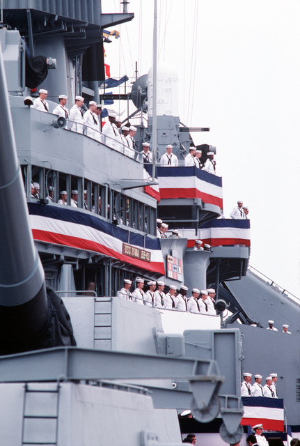 Crew members man the rails of the USS IOWA (BB 61) during the battleship's recommissioning ceremony. One of the ship's Phalanx 20 mm Mark 15 Close-In Weapons Systems can be seen overhead