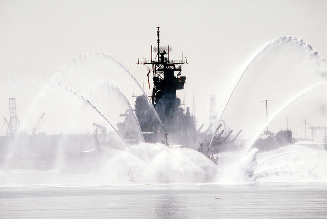 A fireboat spouts fountains of water during the homecoming of the battleship USS NEW JERSEY (BB 62). The ship is returning to home port after 11 months at sea