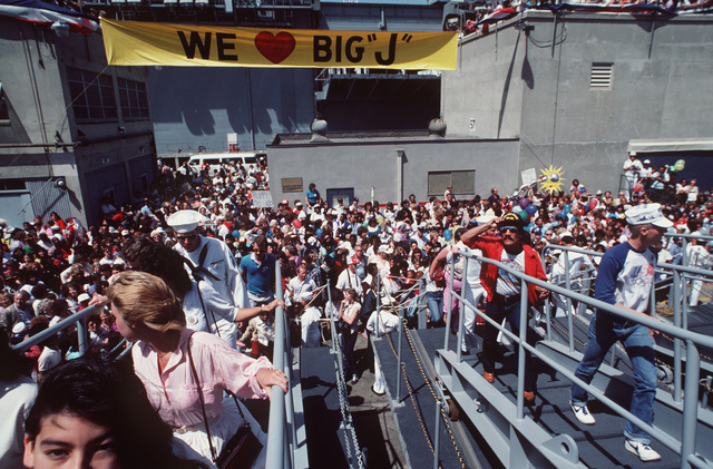 "A large crowd waits to go aboard the battleship USS NEW JERSEY (BB 62) upon the ship's return to home port after 11 months at sea. A banner hanging in front of the amphibious assault ship USS PELELIU (LHA 5) proclaims, ""We Love Big J."""