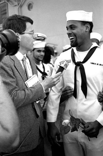 A local television report interviews SEAMAN Desi Wilson upon his return to home port after 11 months at sea aboard the battleship USS NEW JERSEY (BB 62)