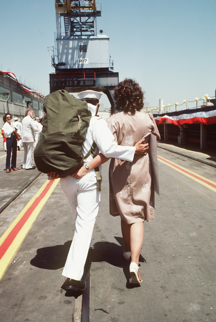 A sailor walks arm-in-arm with a loved one upon returning to home port after 11 months at sea aboard the battleship USS NEW JERSEY (BB 62)