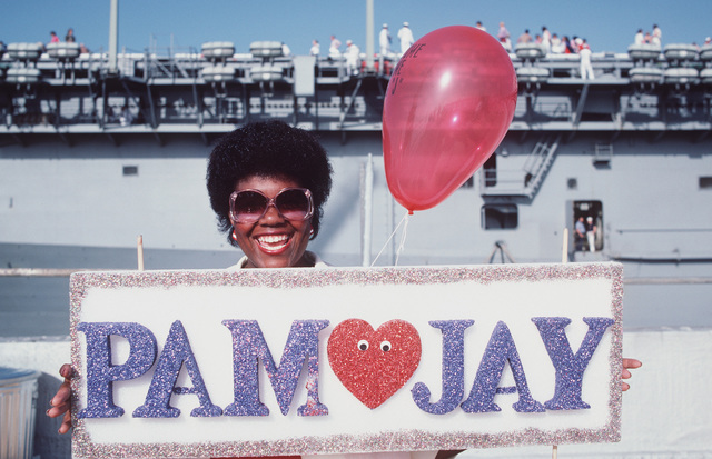 Pat Thomas, wife of Fireman (FN) Jonathan Thomas, holds up a sign welcoming her husband back to home port after 11 months at sea aboard the battleship USS NEW JERSEY (BB 62). A portion of the amphibious assault ship USS PELELIU (LHA 5) can be seen in the background
