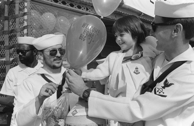 """Sonar Technician 3rd Class (ST3) Robert Johnson gives three-year-old Kirsten Coons a """"Welcome Home Big J"""" balloon during the homecoming of the battleship USS NEW JERSEY (BB 62). Kirsten's father, a NEW JERSEY crewmember, is returning to home port after 11 months at sea"""