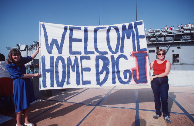 Teresa Mason and Michelle Wright hold up a sign welcoming the battleship USS NEW JERSEY (BB 62) back to home port after 11 months at sea. Teresa's husband, Boilerman Technician 3rd Class (BT3) Kevin Mason, is a crewman aboard the NEW JERSEY. A portion of the amphibious assault ship USS PELELIU (LHA 5) can be seen in the background