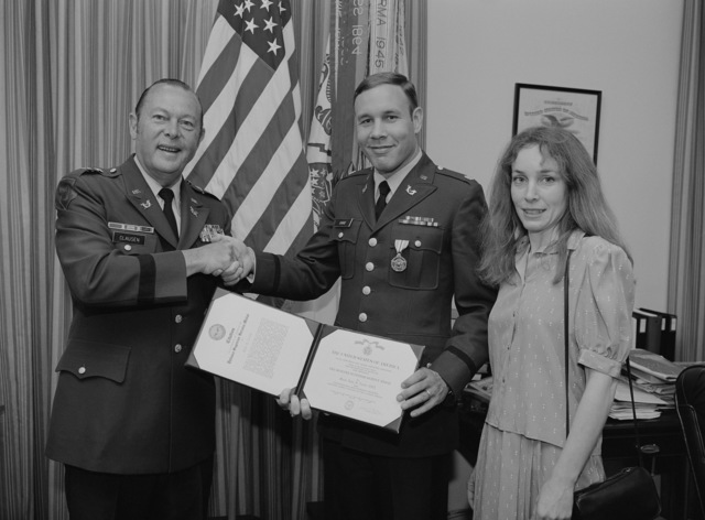 Major General (MGEN) Hugh J. Clausen, Army judge advocate general, presents the Defense Superior Service Medal to Major (MAJ) John S. Cooke, the Army representative on the Joint Service Committee on Military Justice.  Cooke's wife, Melinda, stands to his left