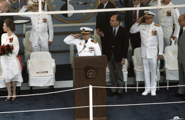 Distinguished guests stand and officers salute as the nuclear-powered attack submarine USS SALT LAKE CITY (SSN 716) is placed in commission. Front row, left to right, are Kathleen Garn, sponsor; Captain Robert I. Itkin, Commanding Officer; Senator Jake Garn, R-Utah; Rear Admiral Stanley G. Catola, Commander, Submarine Group 6; and Governor Scott M. Matheson of Utah