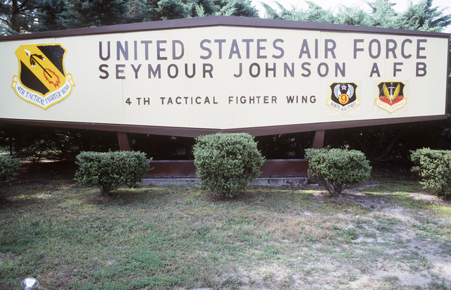 Front view of the entrance sign to the main gate identifying the base and displaying the official emblems (left to right) of the 4th Tactical Air Wing, the Ninth Air Force and the Tactical Air Command