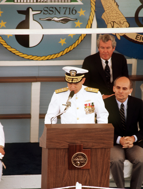 Rear Admiral Stanley G. Catola, Commander, Submarine Group 6, addresses guests attending the commissioning ceremony for the nuclear-powered attack submarine USS SALT LAKE CITY (SSN 716). Seated behind him are Senator Garn, R-Utah, front, and Edward J. Campbell, rear, President and Chief Executive Officer of the Newport News Shipbuilding Co