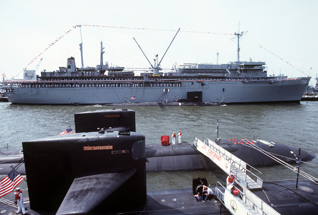 The Los Angeles Class nuclear-powered attack submarines USS CINCINNATI (SSN-693) and USS MEMPHIS (SSN-691) display ensigns and union jacks during the commissioning ceremony for their sister ship, the USS SALT LAKE CITY (SSN-716). Moored alongside the submarine tender USS L.Y. SPEAR (AS-36) is the nuclear-powered attacks submarine USS RICHARD B. RUSSELL (SSN-687)