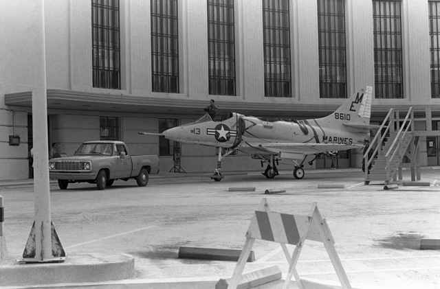 A pick-up truck tows an A-4 Skyhawk aircraft past Building Number One. The jet, formerly on exhibit at the Navy-Marine Corps and Coast Guard Museum, has been donated to Encinal High School in Alameda, California