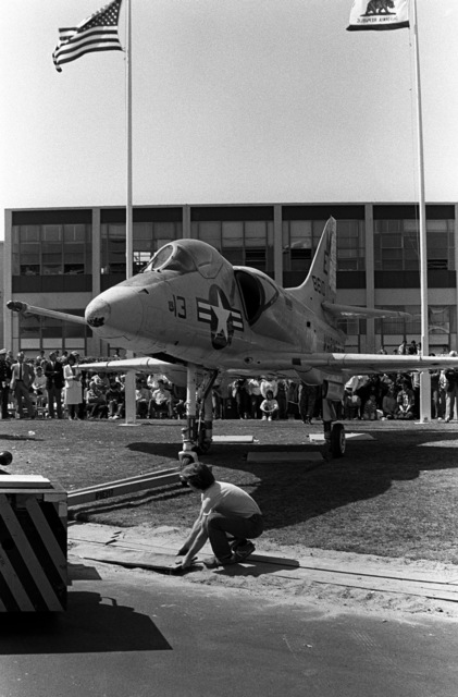 An A-4 Skyhawk aircraft is backed into its new home on the front of Encinal High School. The aircraft, formerly on exhibit at the Navy-Marine Corps and Coast Gurad Museum at Naval Air Station Treasuer Island, California, has been donated to Encinal High School
