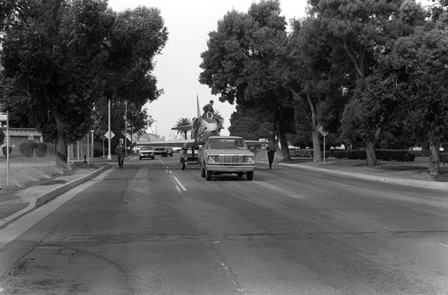 Front view of an A-4 Skyhawk aircraft being towed down California Avenue. The aircraft, formerly on exhibit at the Navy-Marine Corps and Coast Guard Museum, has been donated to Encinal High School in Alameda, California