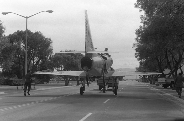 Rear view of an A-4 Skyhawk aircraft being towed down California Avenue. The aircraft, formerly on exhibit at the Navy-Marine Corps and Coast Guard Museum, has been donated to Encinal High School in Alameda, California