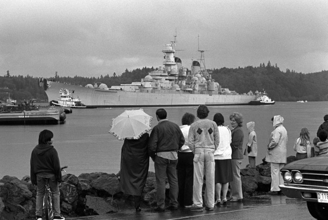 Spectators watch tugs guide the battleship USS MISSOURI (BB 63) away from the dock as it begins the trip to Long Beach Naval Shipyard, California, where it is scheduled to begin reactivation/modernization construction