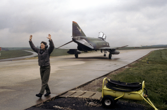 Sergeant Debra L. Spencer, a crew chief with the 26th Aircraft Generation Squadron, directs RF-4C Phantom II aircraft into position for a final check prior to takeoff during Exercise SALTY BEE