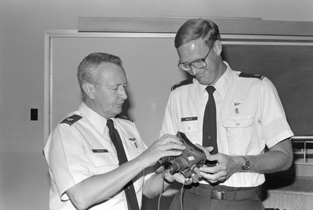 Colonel Thomas J. Tredici (left) explains the mechanics of the AN/PVS-5A night vision goggles to Major Miller. The goggles are being tested by the US Air Force School of Aerospace Medicine's Clinical Services Division for possible use in combat