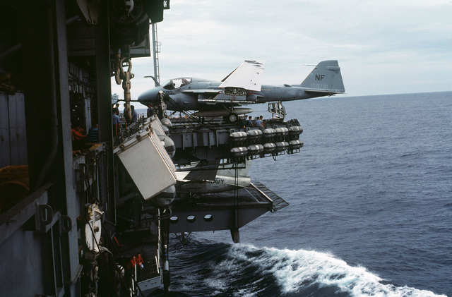 A left side view of an A-6 Intruder aircraft on the flight deck of the aircraft carrier USS MIDWAY (CV 41). An A-7 Corsair II aircraft is on the starboard elevator