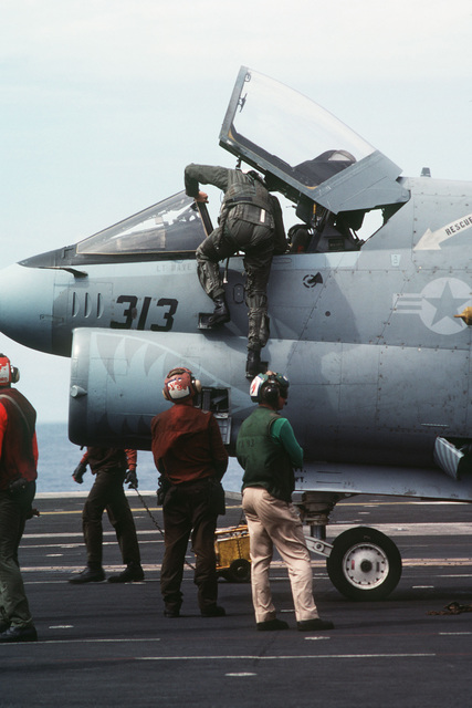 A pilot climbs into an A-7 Corsair II aircraft on the flight deck of the aircraft carrier USS MIDWAY (CV41)
