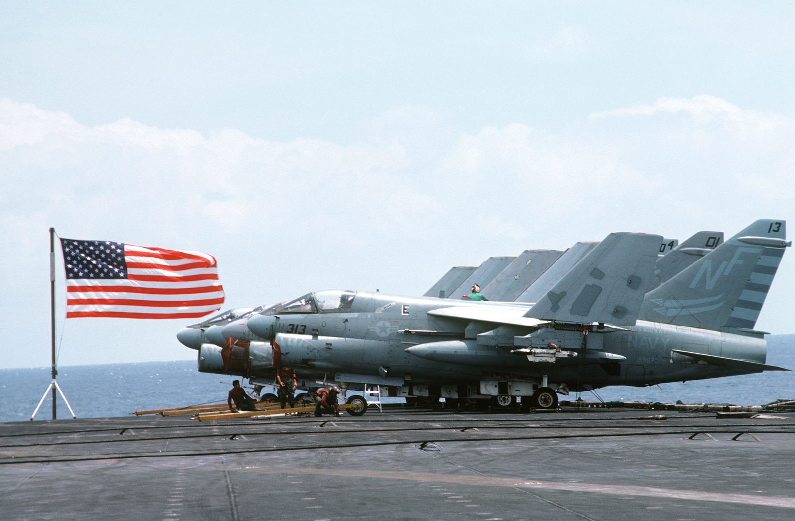 A row of A-7 Corsair II aircraft on the flight deck of the aircraft carrier USS MIDWAY (CV 41)