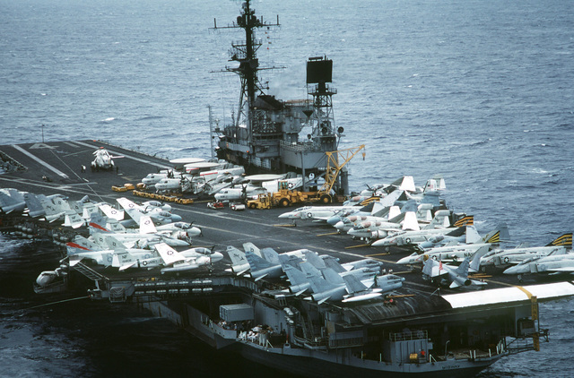 An elevated view of the flight deck of the aircraft carrier USS MIDWAY (CV 41). Aircraft on the deck include, from front to back, (right side): F-4 Phantom II aircraft, EA-6B Prowler aircraft, A-6 Intruder and E-2 Hawkeye aircraft. Planes on the left side include A-7 Corsair II aircraft and A-6 Intruder aircraft. An SH-3 Sea King helicopter is visible in the background