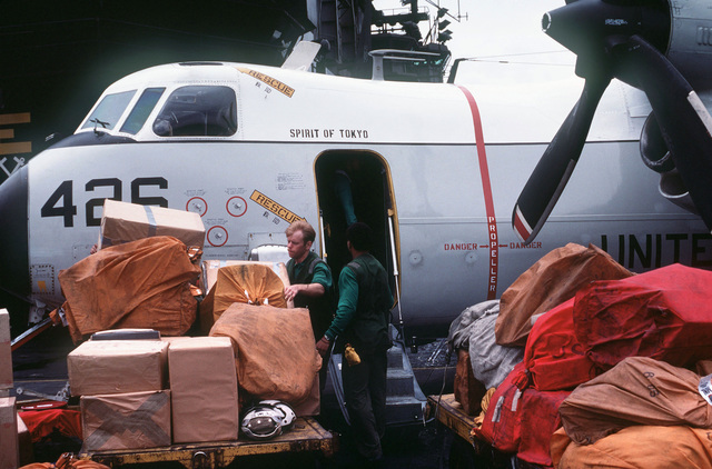 Cargo on pallets beside a C-2 Greyhound aircraft, on the flight deck of the aircraft carrier USS MIDWAY (CV 41)