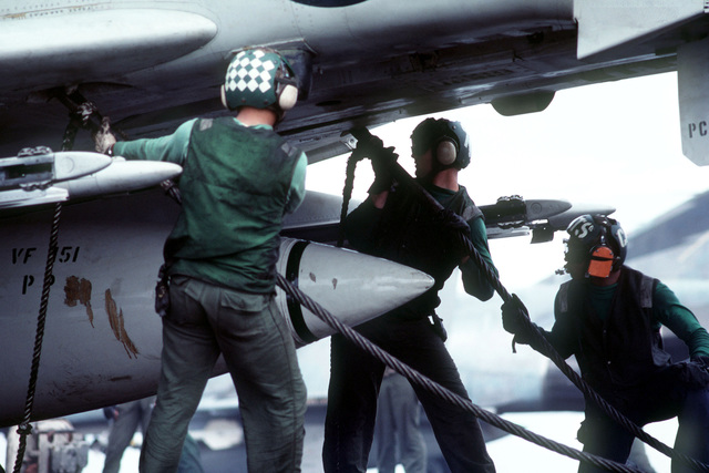 Crewman attach a launching bridle to an F-4 Phantom II aircraft from Fighter Squadron 151 (VF-151) on the aircraft carrier USS MIDWAY (CV41)