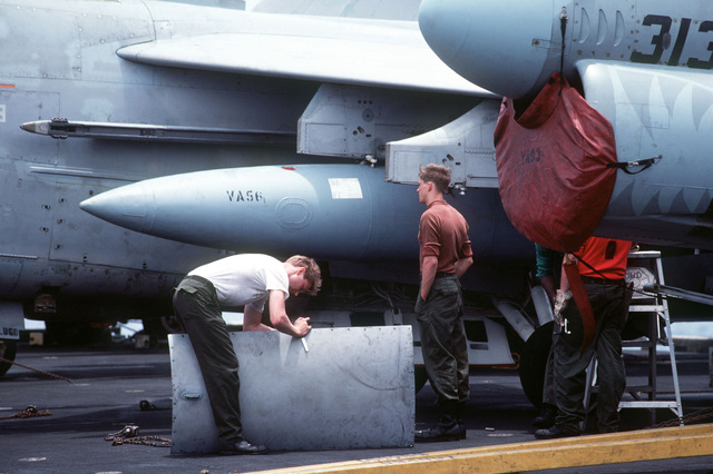 Members of Light Attack Squadron 56 (VA-56) perform maintenance on an A-7 Corsair II aircraft, aboard the aircraft carrier USS MIDWAY (CV 41)
