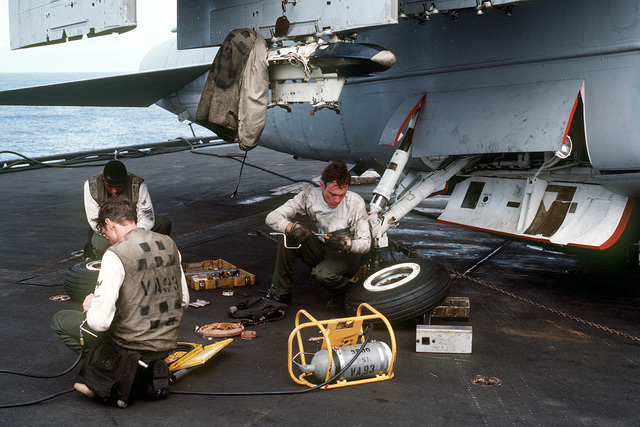 Members of Light Attack Squadron 93 (VA-93) maintenance crew service, an A-7 Corsair II aircraft aboard the aircraft carrier USS MIDWAY (CV 41)
