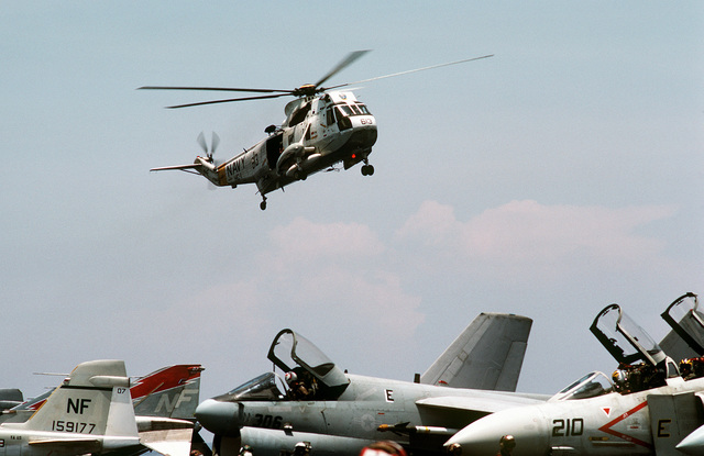 Right front view of a SH-3 Sea King helicopter in-flight above the aircraft carrier USS MIDWAY (CV-41). Aircraft on the deck include (right to left) F-4 Phantom II, A-7 Corsair II and an A-6 Intruder